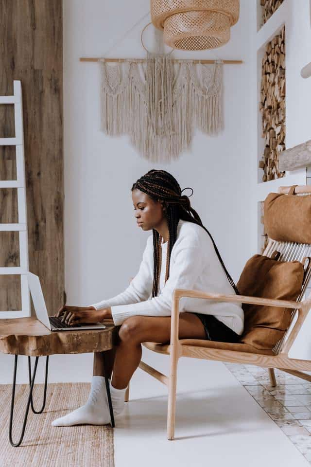 black woman sits forward in her chair, intently watching her laptop computer with her fingers ready to type.