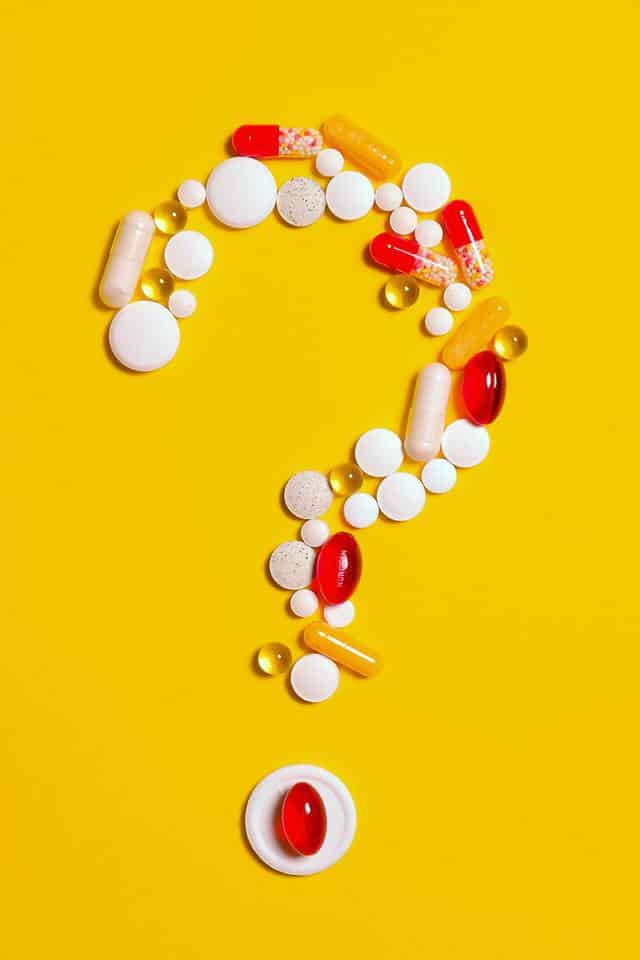 a collection of a variety of pills ranging from white to red, arranged to form a question mark all on a yellow background
