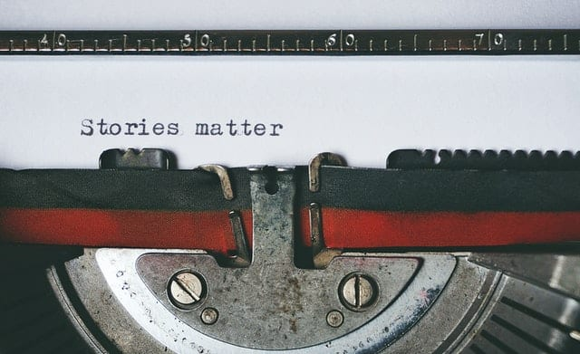 typewriter, with the words 'stories matter' typed on the page
