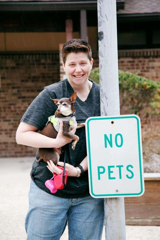 A person holds their dog next to a sign that reads 'no pets'