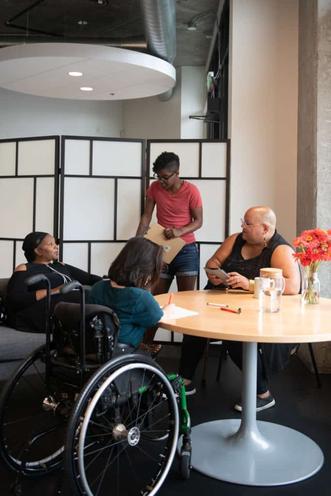 Four disabled people of color gather around a table during a meeting. A Black woman sitting on a couch speaks with a neutral expression while the three others (a South Asian person sitting in a wheelchair and taking notes, a Black non-binary person sitting in a chair with a tablet and cane, and a Black non-binary person standing with a clipboard) listen