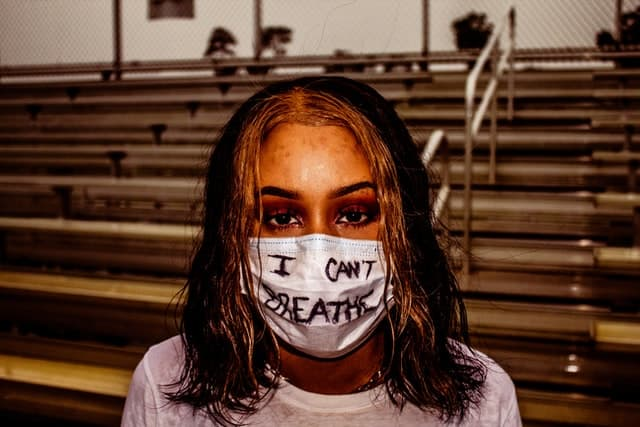woman of color wears a facemask with the words 'I can't breathe' written on it
