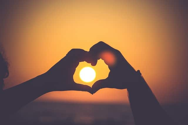 two hands create a heart-shape around the sun, visible in the distance.