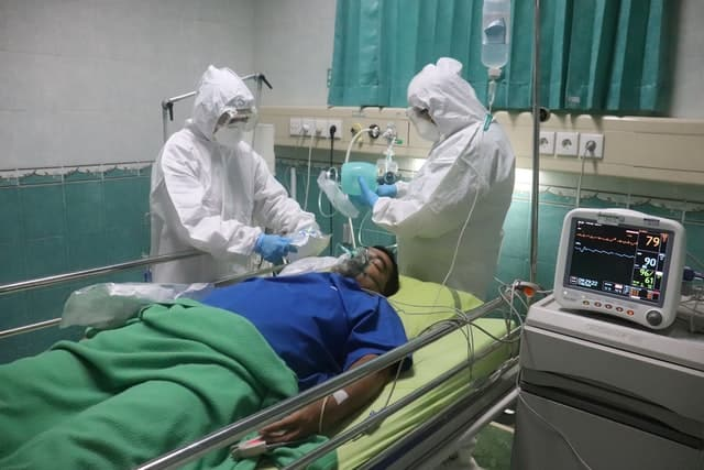 two medical professionals in full protective gear stand near the head of a patient with an oxygen mask, discussing treatment.
