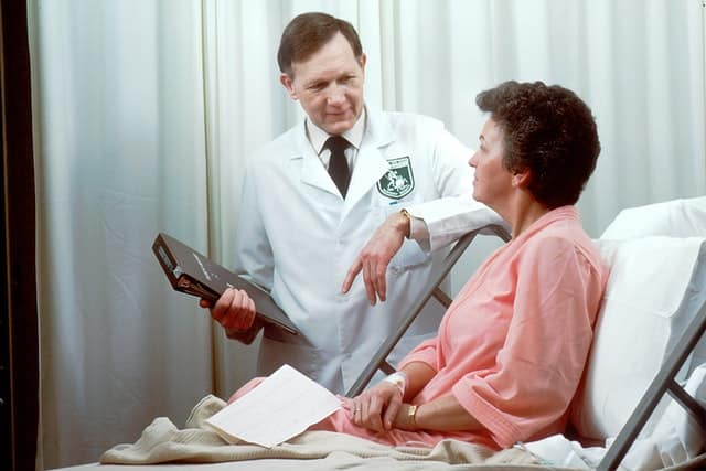 doctor stands beside patient in a hospital bed.  The two of them are conversing