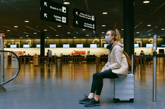 woman sits on a hard-cased suitcase, with a surgical mask on at an airport.