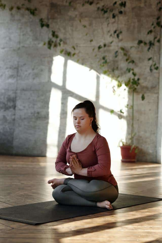 A woman with Down Syndrome sits on a yoga mat with crossed legs and her hands in a prayer position