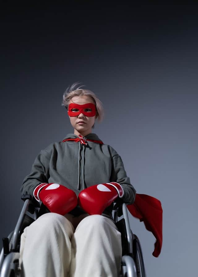 woman in a wheel chair with a determined look on her face, a red cape flying behind her, and a red mask around her eyes.  She is wearing red boxing gloves