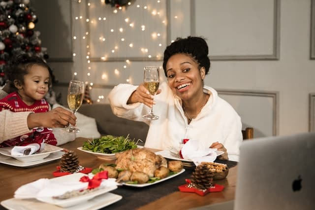 a woman and her spouse(mostly offscreen with just a hand visible) toast champagne flutes towards their computer, with their young daughter sitting between them eating dinner