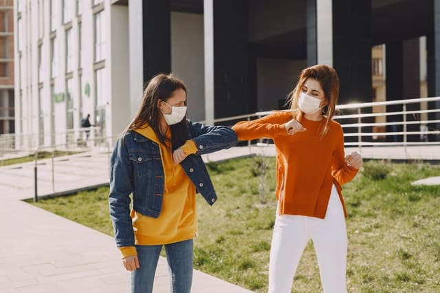 two women bump elbows in greeting while wearing medical masks