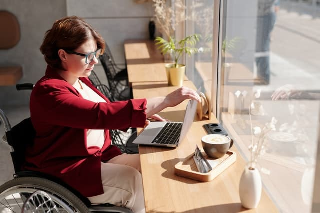 woman in a wheelchair dressed in business clothes looks at her laptop.