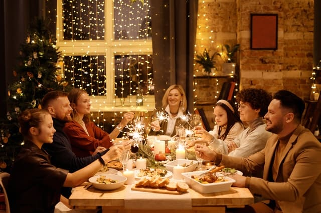 An extended family sits down to a festive meal together with holiday lights in the background