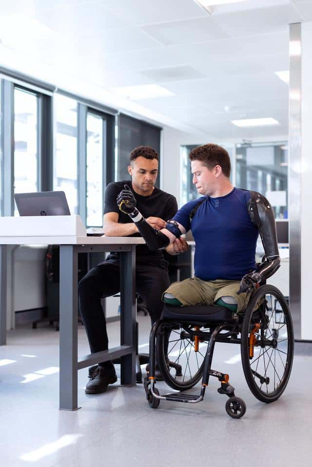 legless man in wheelchair is having prosthetic arms fitted by a technician.