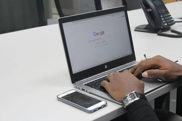 A laptop with the google search screen visible.  A pair of hands are on the keyboard poised to type