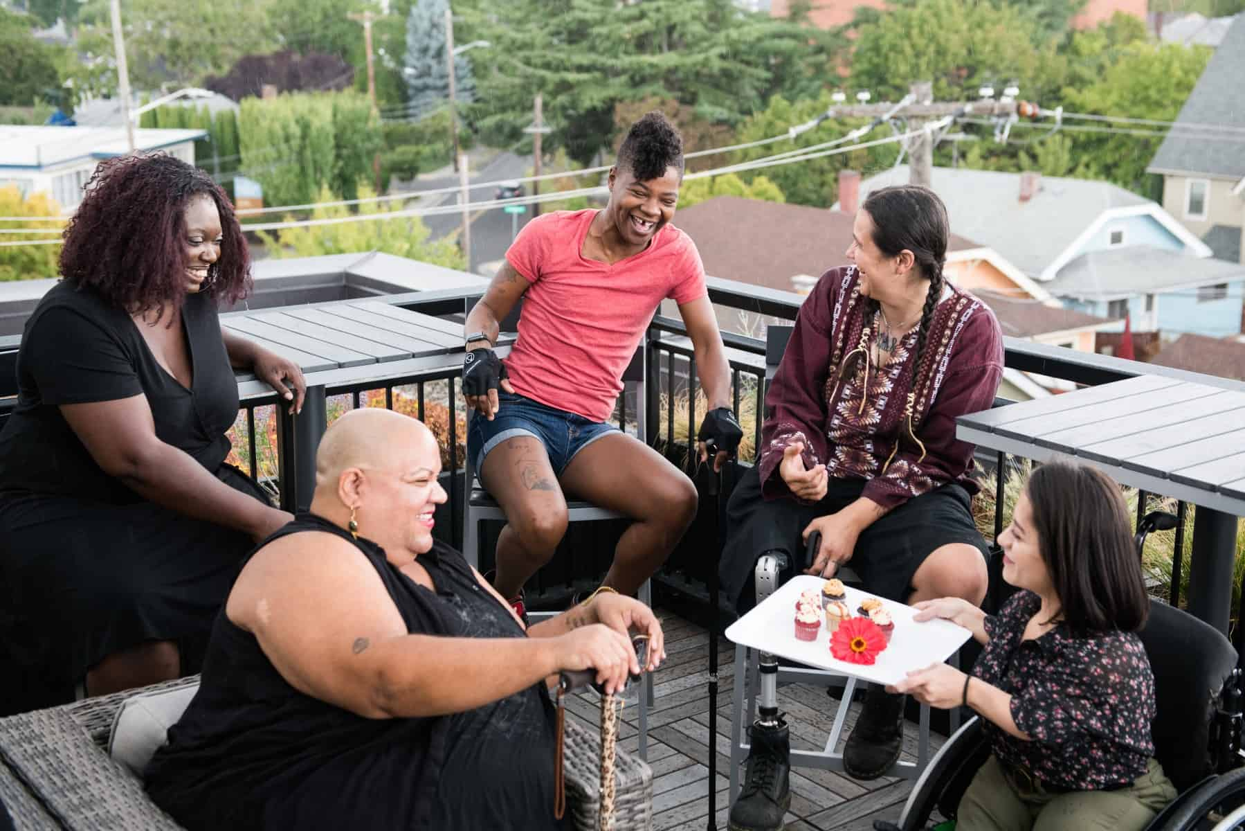 A South Asian person in a wheelchair brings mini cupcakes out on a platter to four other excited disabled people of color. They are all sitting around a rooftop deck.