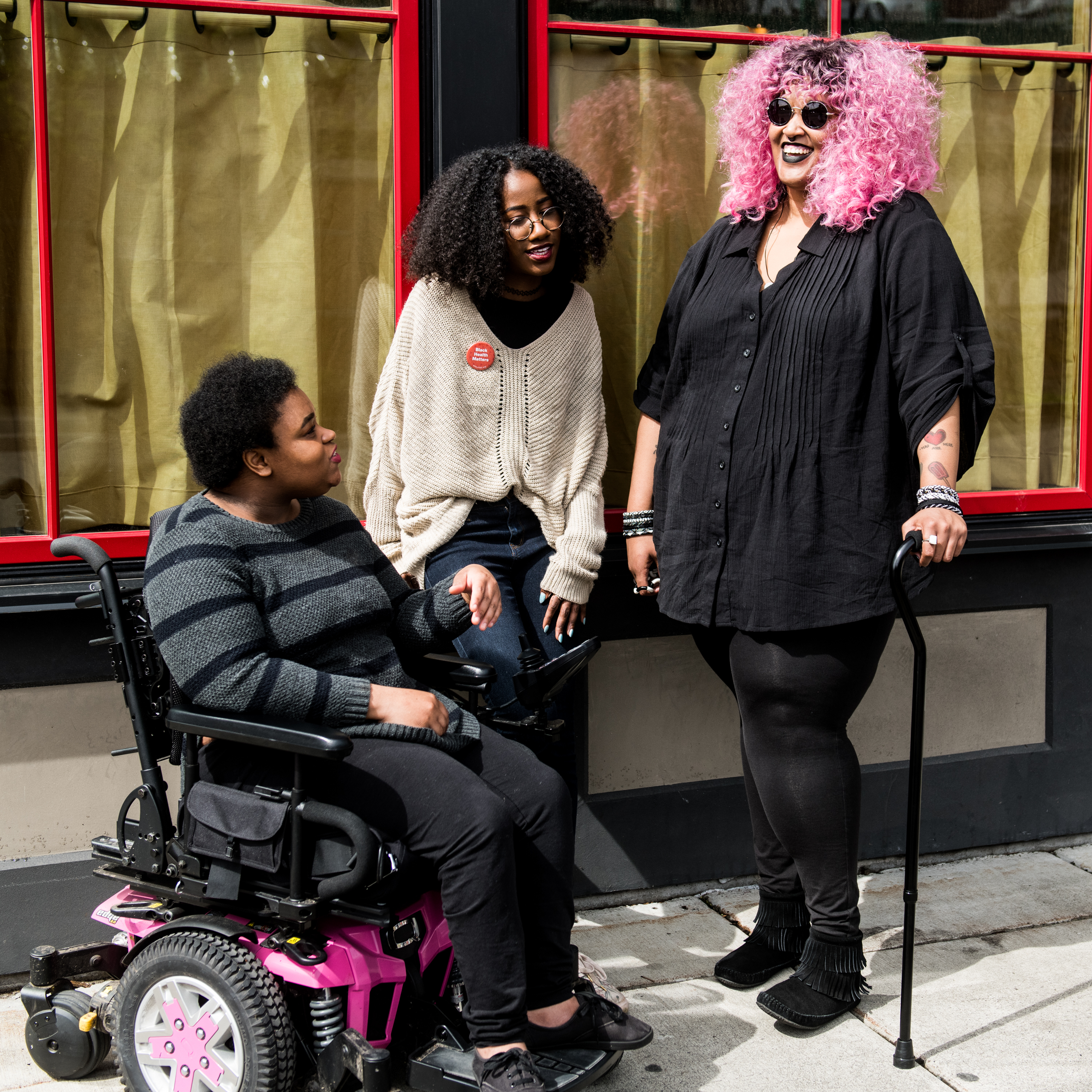 Three Black and disabled folx (one woman in a power wheelchair, one woman leaning against a wall, and one non-binary person standing with a cane) engaged in converation. All three are outdoors and in front of a building with two large windows.