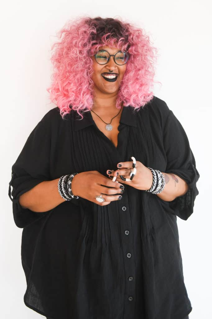 Torso crop of a Black and Indigenous austistic non-binary person laughing while using a tangle stim toy. She is rocking pink ombré hair, glasses, black lipstick, black nail polish, tattoos, bracelets, a septum ring, and a black tunic.