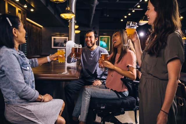Four people stand and sit together at a bar, smiling and raising drinks. They are a diverse group, and one of the women is a wheelchair user