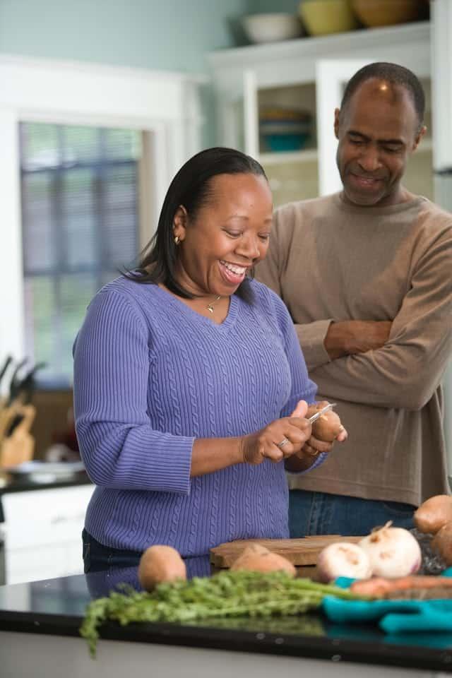 A black woman peels potatoes while her husband looks on