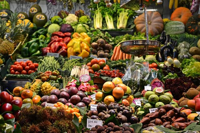 Inside a produce market - a scale is visible in the foreground with a huge variety of fruits and vegetables visible behind and around it.