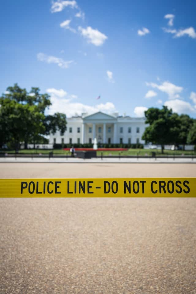 the whitehouse with yellow caution tape in front of it reading 'police line do not cross'