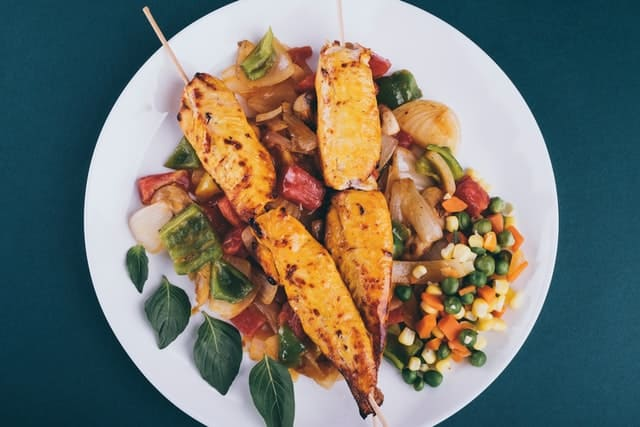 a plate on a green background.  The focus is on the contents of the plate: skewered chicken atop a mound of colorful vegetables