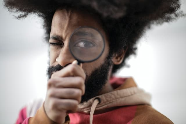 Black man holds a magnifying glass in front of his left eye, expression serious