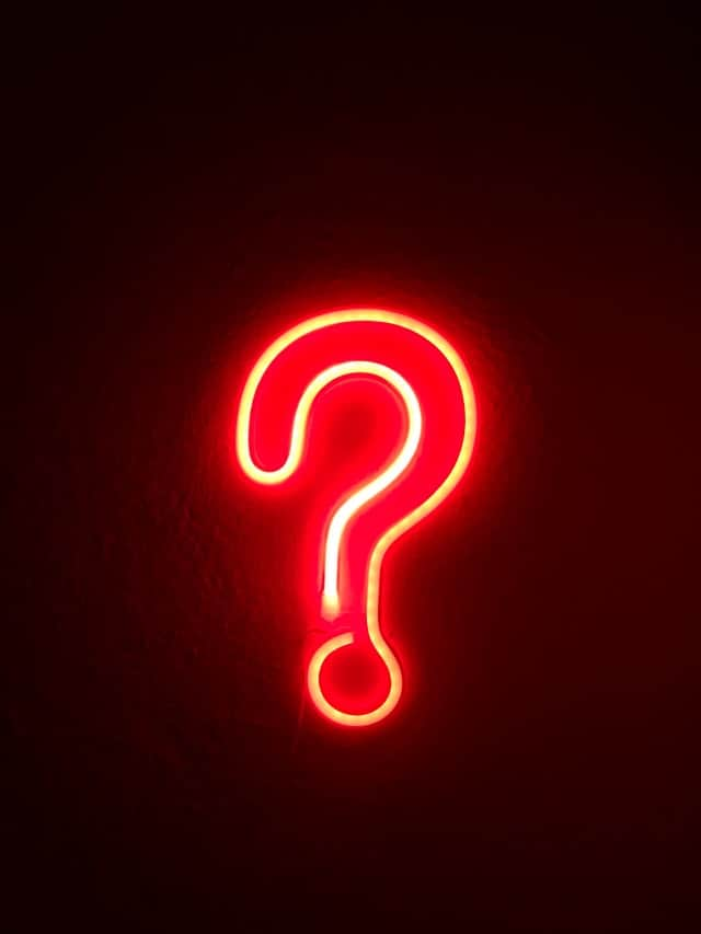 a neon question mark on a black background