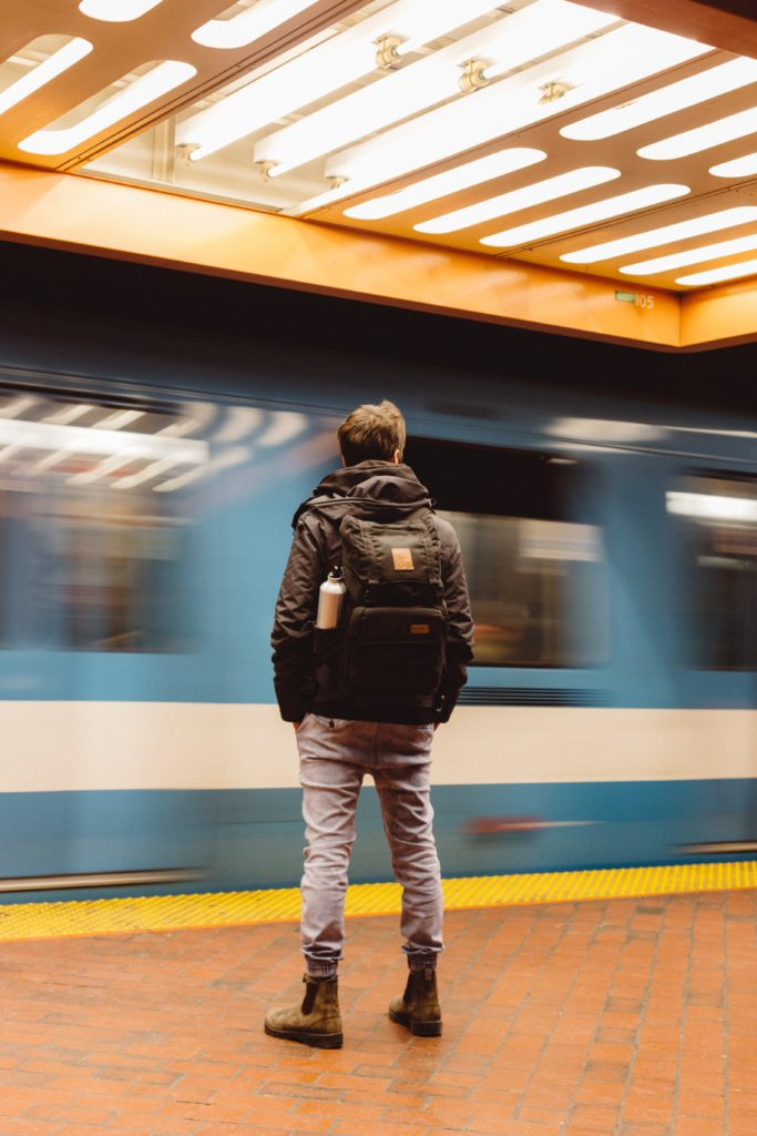 a man stands in a subway station wearing jeans, a coat and a medium-sized backpack with a water bottle on one side.