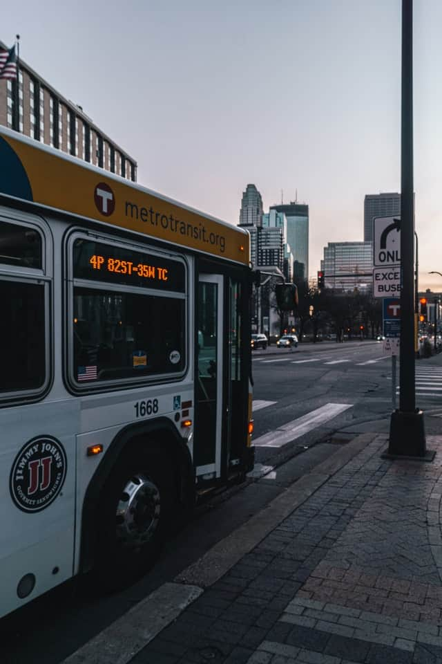 a city bus pulls up to a bus stop, with its route information clearly visible in lighted scrolling text