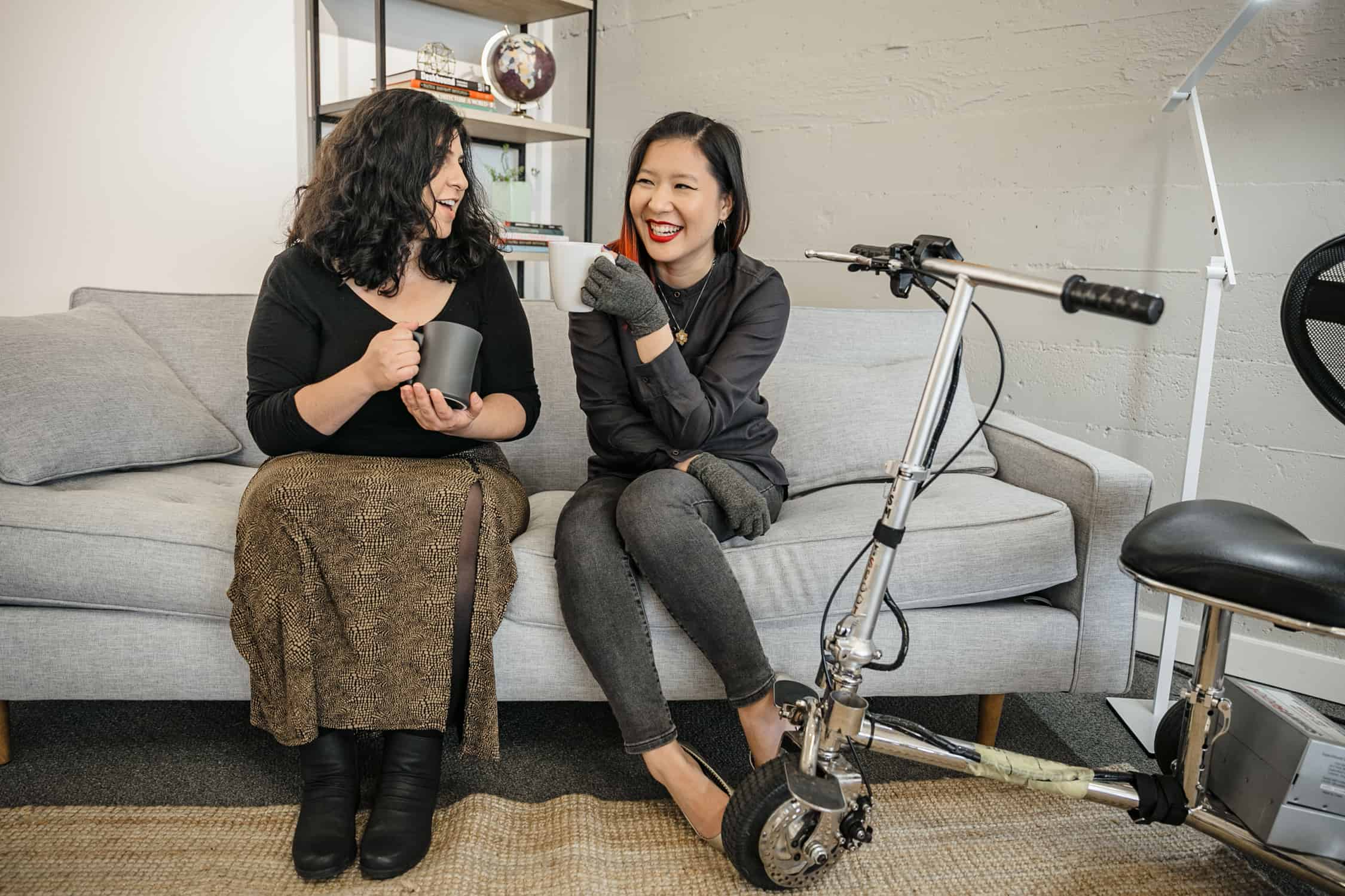 A Latinx disabled woman and an Asian disabled woman chat and sit on a couch, both holding coffee mugs. An electric lightweight mobility scooter rests on the side.
