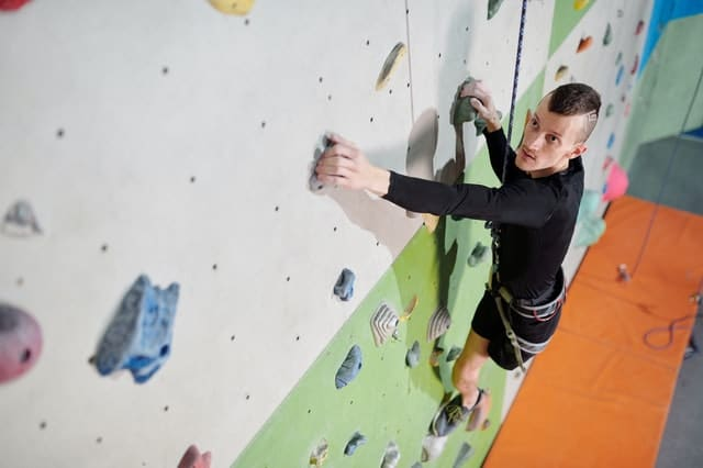 man in harness climbs an indoor rock wall.  He is missing  his left leg.