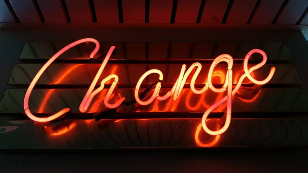 neon orange sign that reads 'change'