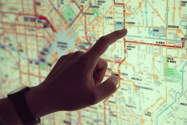 A hand is visible against the backlit map behind it. The finger points to a bus stop on the routes disaplayed