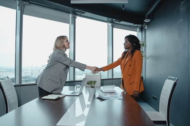 two women shake hands across a table.