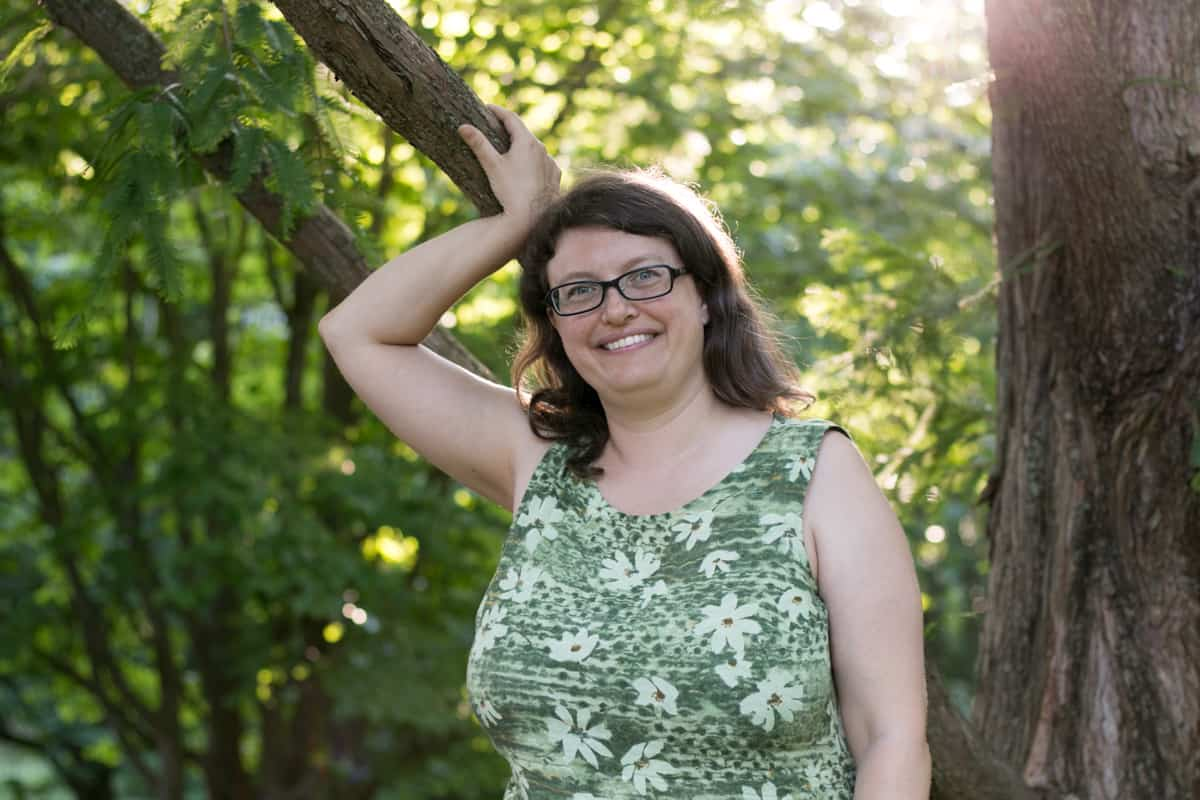 Alison, a white woman with glasses and long brown hair stands with her right hand leaning against a tree branch. She is wearing a green and white dress with trees in the background