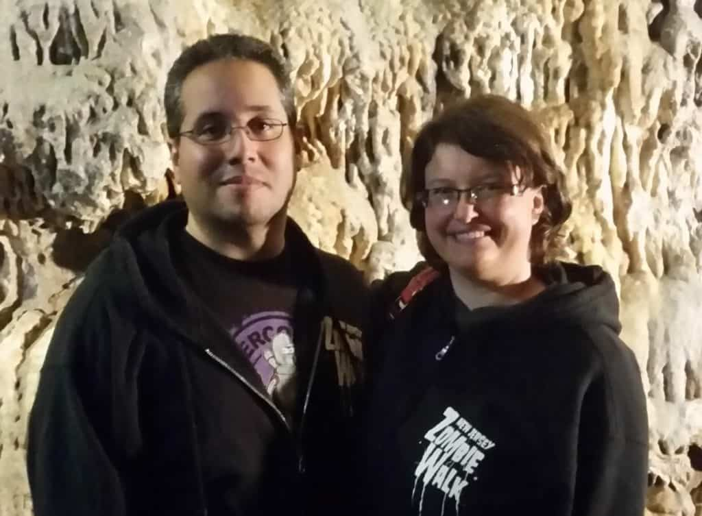 Al and Alison stand beside one another inside a cave.
