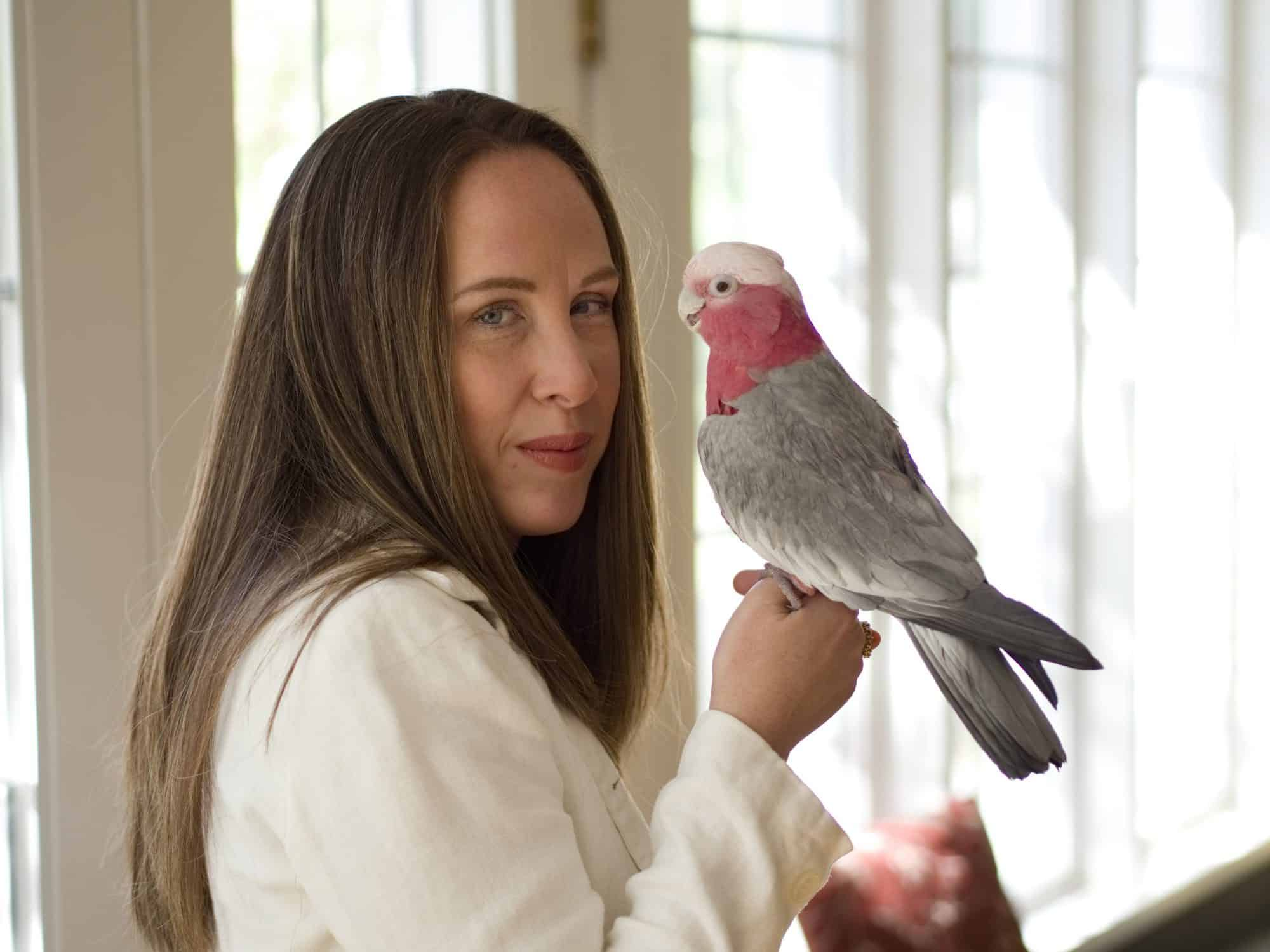 Tatiana(white woman with honey-brown hair) smiling while holding her rose breasted cockatoo. The picture is cropped at chest-height.
