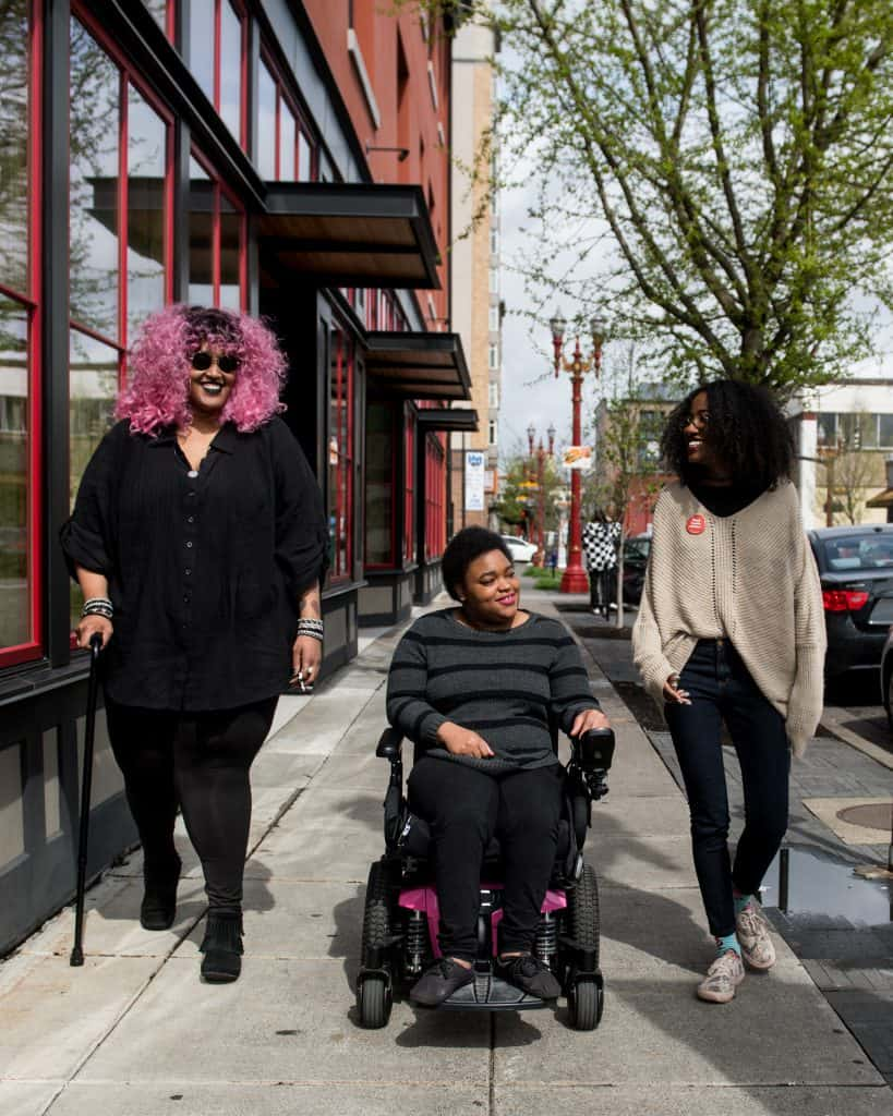 Three Black and disabled folx smiling at each other while strolling down a sidewalk side by side. On the left, a non-binary person walks with a cane in one hand and a tangle stim toy in the other. In the middle, another non-binary person rolls along in their power wheelchair. On the right, a woman walks and gestures.