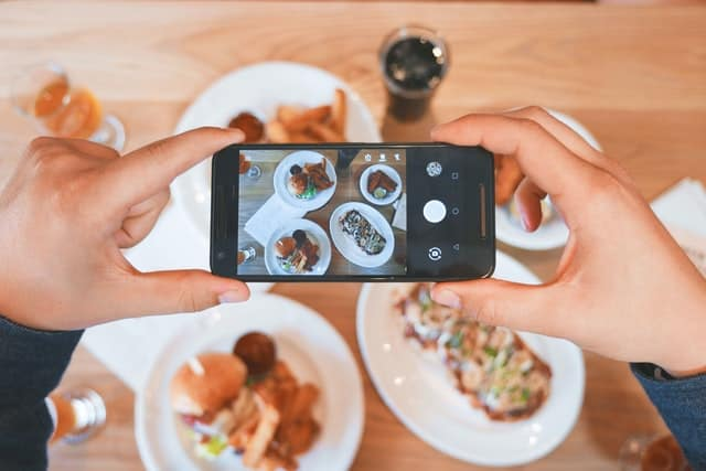 person snapping a picture of their meal.