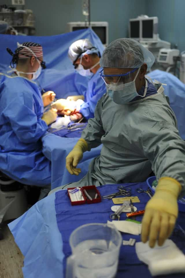 view inside of an ER during surgery - one person in scrubs looks and reaches behind himself to grab a piece of equipment.