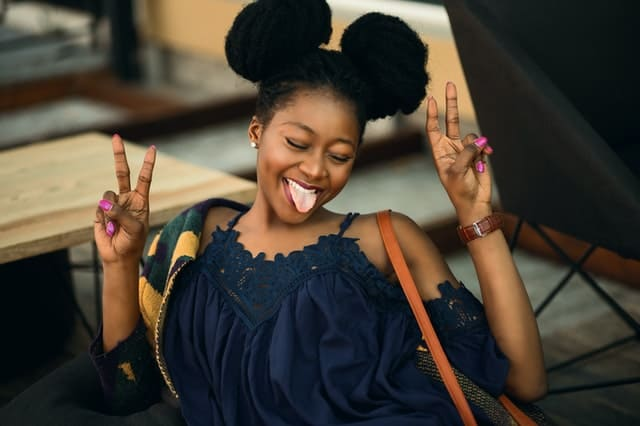 Black woman with her hair up in two puffs smiles broadly with her tongue sticking out as she makes the 'v' sign with the fingers of both hands