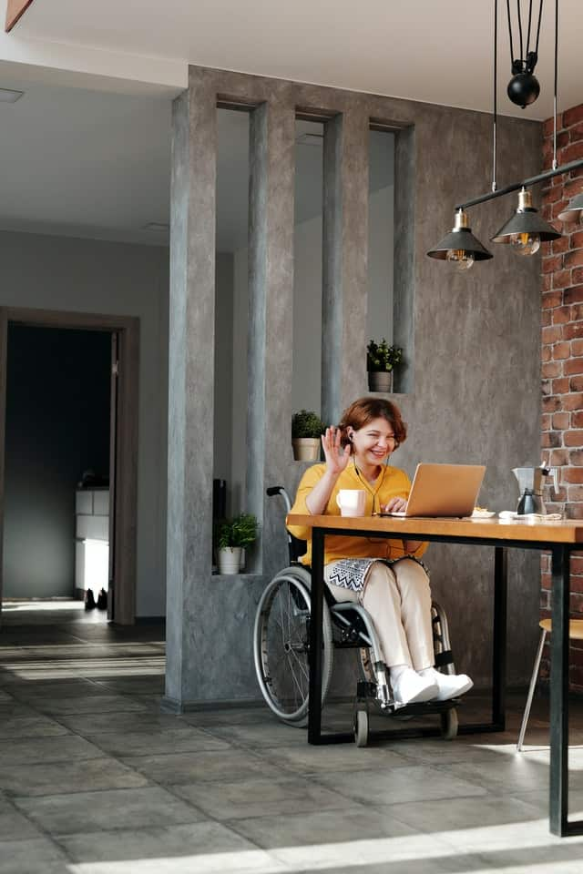 woman in a wheelchair is pictured in a wide shot.  she has her computer open and is waving to somebody on the screen