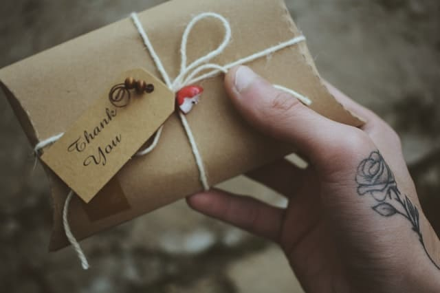 a brown-wrapped present with the words 'thank you' written on it.  The hand holding the present has a lovely rose tatooed on it