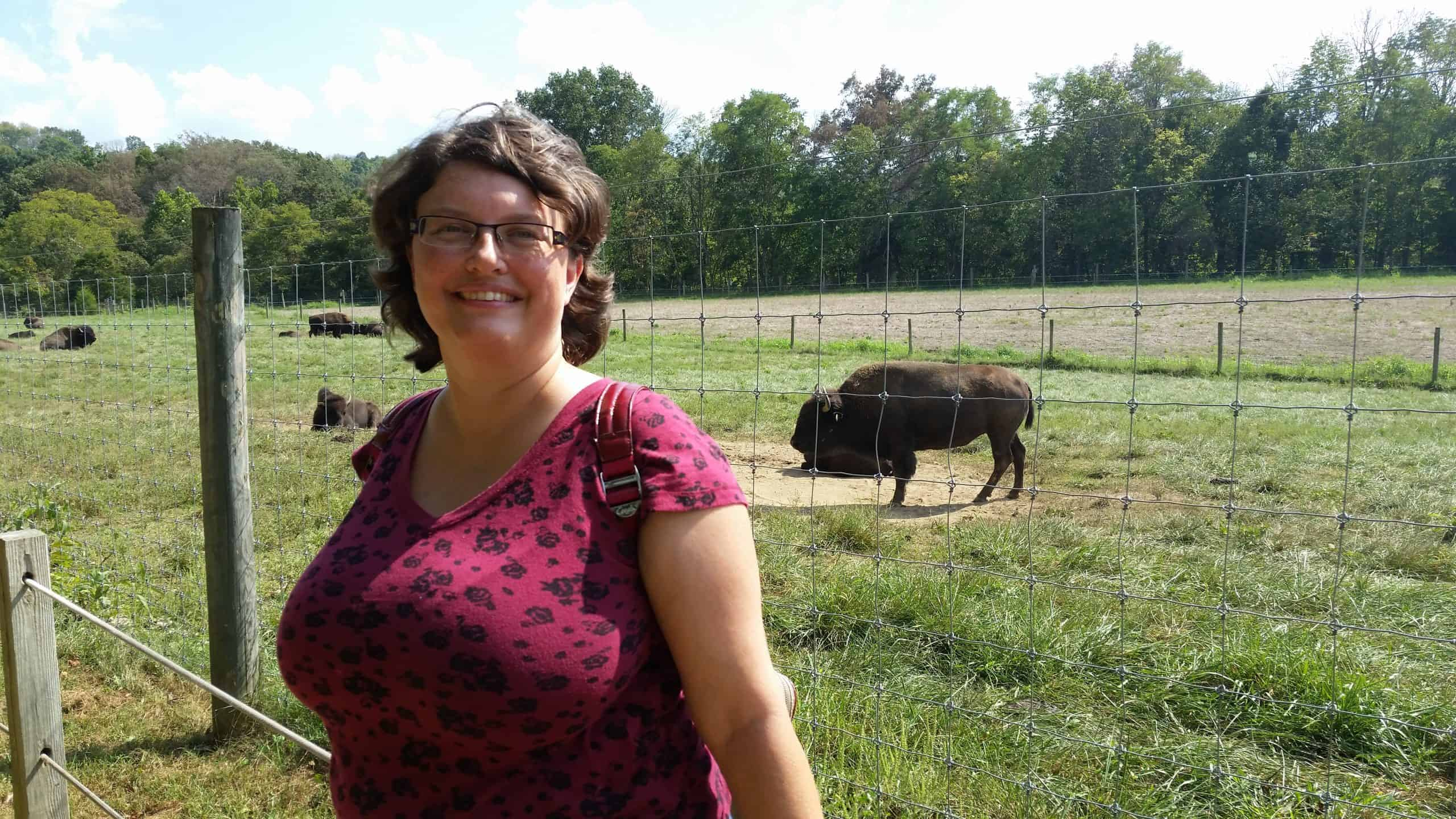 Alison smiles. She has short brown hair in thi picture and is wearing glasses. Bison are visible behind her