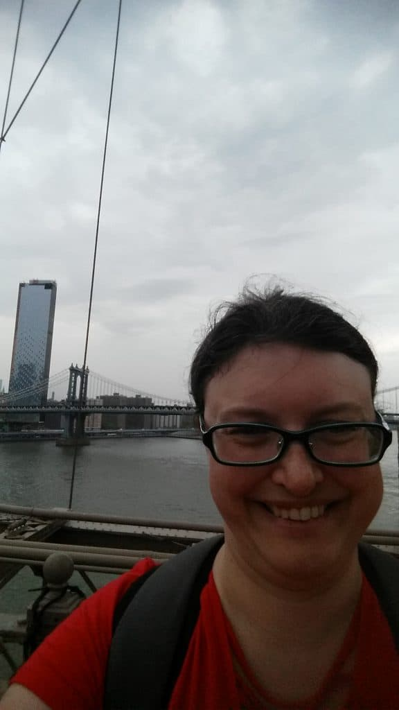 Alison smiles for a selfie atop the Brooklyn bridge.  NYC is visible in the background.