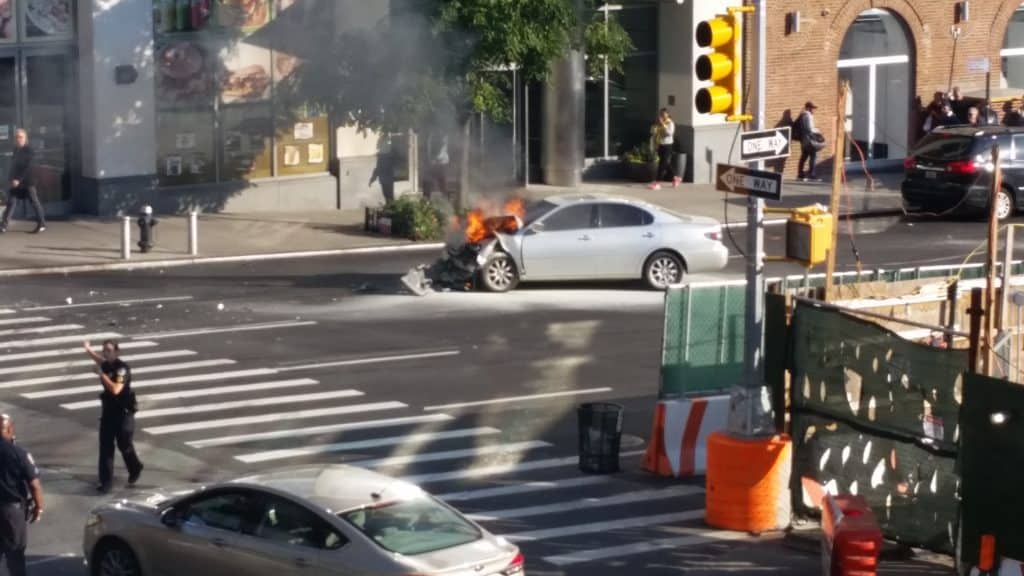A car is visible on the street.  Its engine is on fire, with flames easily visible