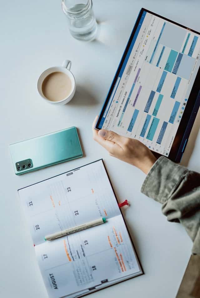 a physical planner sits on a desk, as a person holds their tablet with its calendar app active on it.  Their phone is facing down nearby