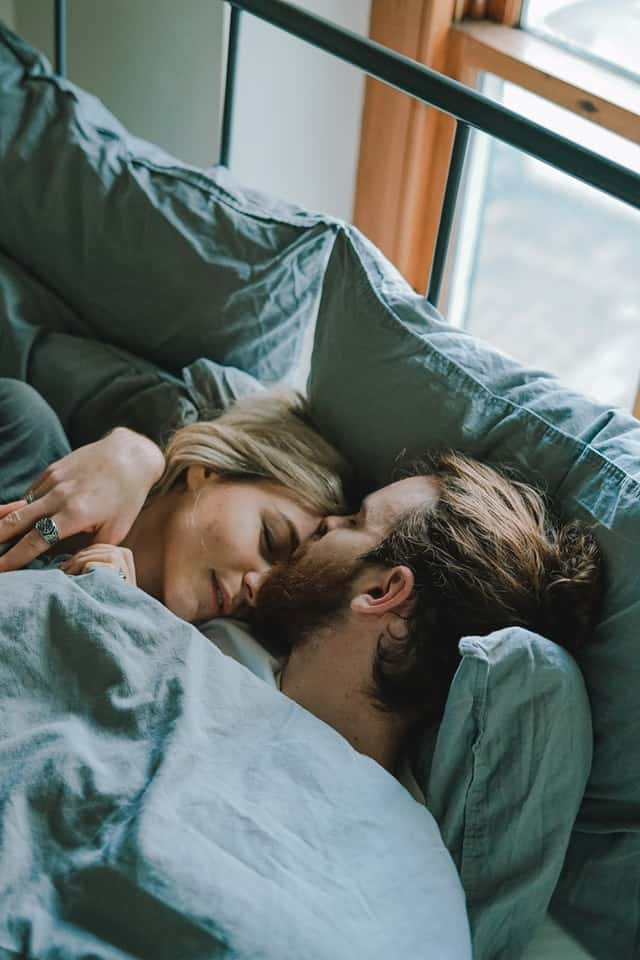 A white man and woman lie in bed cuddled together. He is kissing the top of her head.