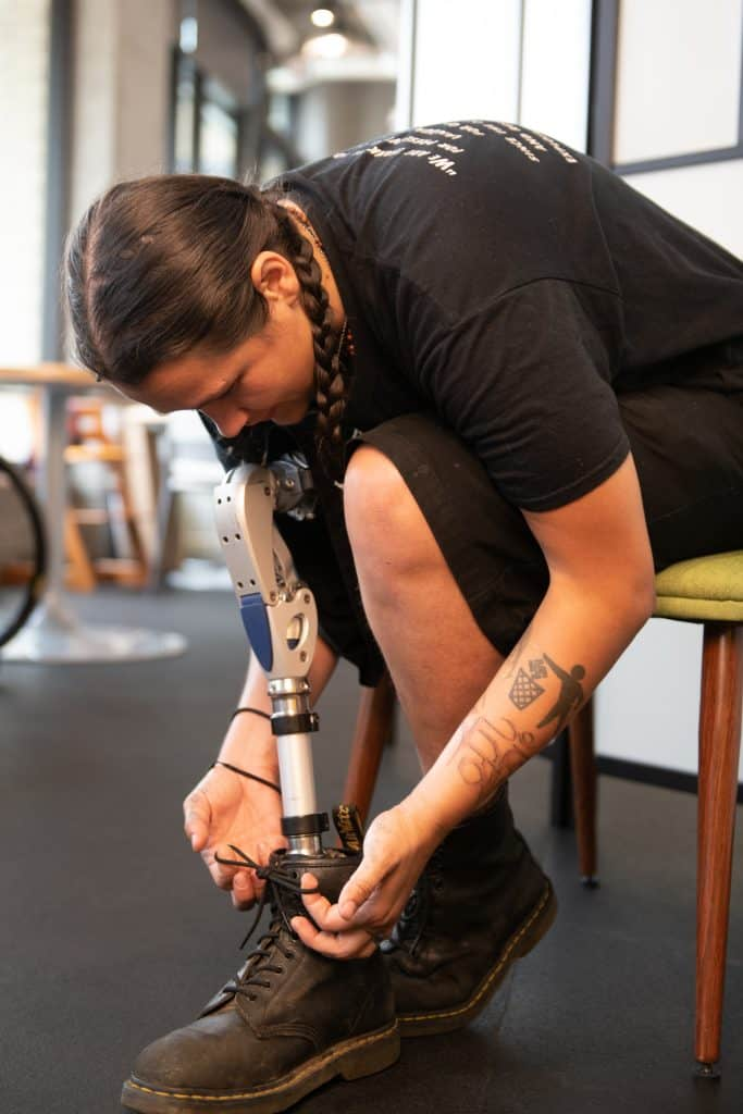 An Indigenous Two-Spirit person ties their shoelaces while sitting in a chair. They are dressed in all black and have braided hair, tattoos, and a prosthetic leg.